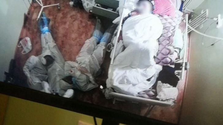 Se hace viral esta imagen de tres sanitarios en el suelo acompañando a una paciente de Covid-19