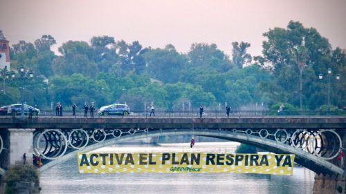 Escaladores de Greenpeace se descuelgan con una pancarta en el puente de Triana